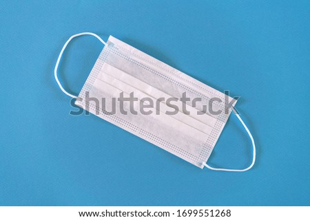 White medical mask on a blue background close-up, protection concept. #1699551268