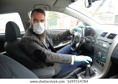 A business man with a protective surgical mask and gloves driving a car during the covid-19 virus outbreak.  #1699554784