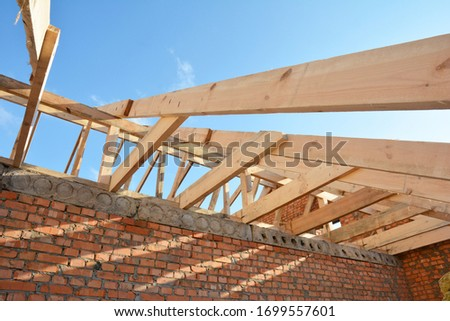 Roofing construction on the stage of roof framing, installation of wooden trusses, eaves, braces and roof beams on a brick house. #1699557601
