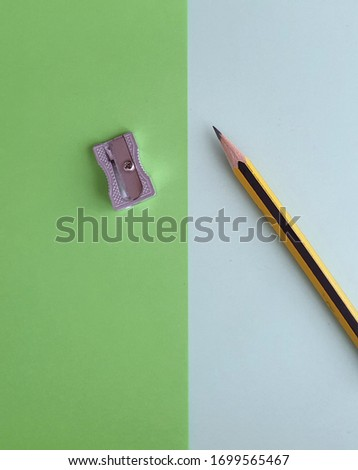 A pencil and a metal pencil sharpener, on two shades of green. Background image for school, high school, university, business, company. Concepts for study, school, office or work.  Top view.