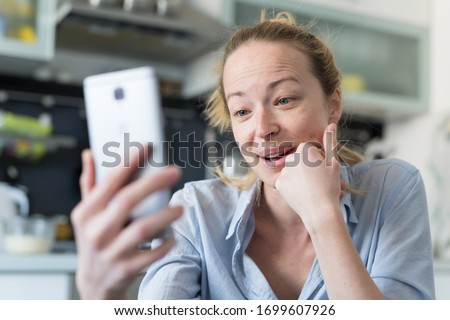 Young smiling cheerful woman indoors at home kitchen using social media apps on phone for video chatting and stying connected with her loved ones. Stay at home, social distancing lifestyle. Royalty-Free Stock Photo #1699607926