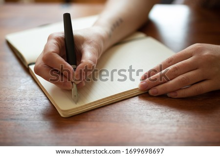 Beautiful female hands writing a journal entry in a diary using an ink fountain pen.  Royalty-Free Stock Photo #1699698697