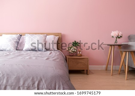 bedroom Interior of room with comfortable bed near pink wall #1699745179