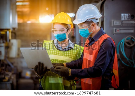 Portrait woman worker and engineer under inspection and checking production process on factory station by wearing safety mask to protect for pollution and virus in factory. #1699747681