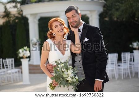 Beautiful wedding couple posing in park #1699750822