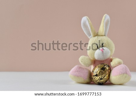 Easter bunny in a hug with Easter eggs. Easter bunny in a hug with Easter eggs. A cute little rabbit with close-up eggs on a beige background with a replica of the space.