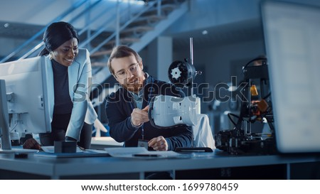 Electronics Development Engineer Working at His Desk, Talks with Project Manager, Shows Mechanism Prototype Construction. Team of Professionals Working in the Modern Technology Designing Agency. Royalty-Free Stock Photo #1699780459