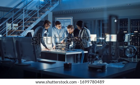 Team of Electronics Development Engineers Standing at the Desk with 3D Printer and PCB Motherboards. Specialists Working on Ultra Modern Industrial Design, Using Advanced Technology. Slow Motion #1699780489