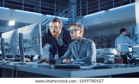 Electronics Development Engineer Uses Personal Computer Talks with Manager, Shows Project. Team of Professionals Use Digital Whiteboard use CAD Software for the Modern Industrial Engineering Design #1699780507