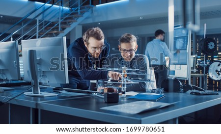 Electronics Development Engineer Talks with Project Manager, they Choose PCB Motherboard to Hold Device Microchip. Team of Professionals Use Tablets and CAD Software for Modern Industrial Design #1699780651