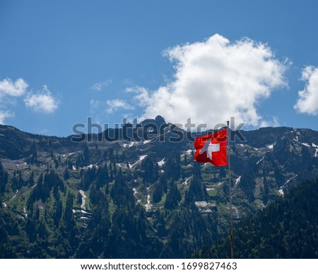 The Swiss flag in front of mountains.