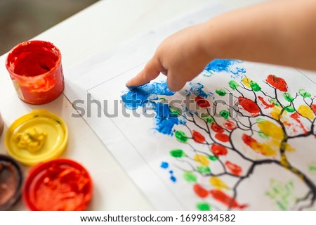 A child draws leafs on a tree. Ideas for drawing with finger paints. Finger painting for kids on white background. Little girl painting by finger hand paint color. Children development concept.  Royalty-Free Stock Photo #1699834582