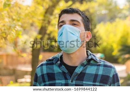 Coronavirus is over, freedom concept. Man holding his mask in the sunshine freedom. Coronavirus ended. We won. No more quarantine. Breathe deep. Take off the mask. Cure. The moment has come. #1699844122