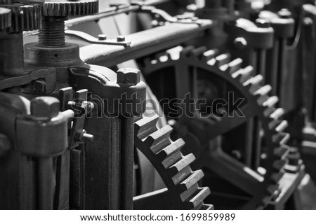 Black and white close-up of a mechanic steel clockwork, showing rotating gear wheels and crankshaft. Picture taken of the ancient money press in the historic Casa da Moneda in Potosi, Bolivia