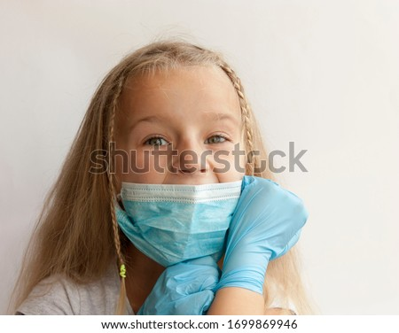 A child in a medical mask and gloves on a white background. Protection from coronavirus, infections, chemicals and poisons. #1699869946