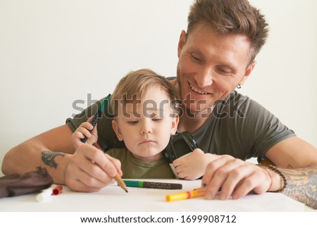Young father helps son at age of two draw, teaches alphabet. A small boy is sitting on his dads lap near white wall in room at table, on piece of paper writing letters and pictures with felt-tip pen.