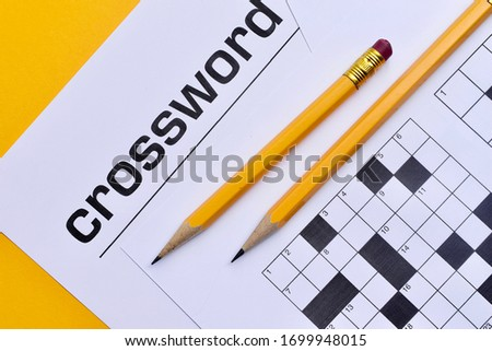 Crossword puzzle and pencils on a yellow background #1699948015