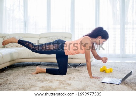 Picture of pretty woman looking at her watch while doing exercise with laptop in living room