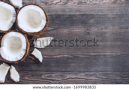 coconut halves, coconut pieces on a wooden background top view. background with split coconuts close-up. coconuts and copy space. coconuts lay flat. #1699983835