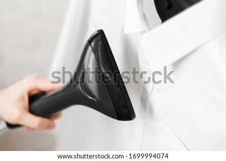 a man puts things in order. holds the garment steamer in his hand and smoothes the jacket after washing Royalty-Free Stock Photo #1699994074