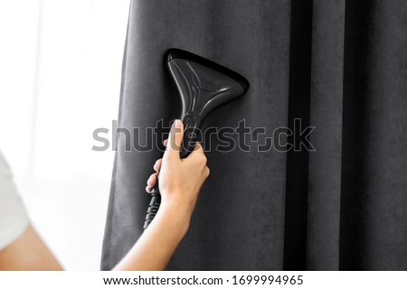 The girl holds a steamer for curtains in her hand. Cleaning of the apartment. macro Royalty-Free Stock Photo #1699994965
