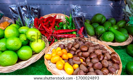fresh vegetables and fruits in a basket at the market, chestnuts, avocado, lime, chili pepper #1700024893