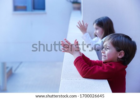 child clapping on the balcony in recognition of the health and cleaning workers Royalty-Free Stock Photo #1700026645