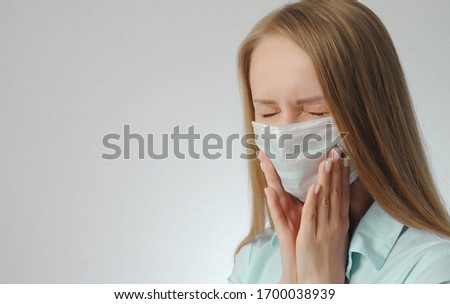 young blonde girl with toothache in medical mask #1700038939