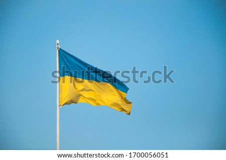 Ukraine flag Silk waving flag of Ukraine made transparent fabric  gold spear on background sunny blue sky real retro photo  Royalty-Free Stock Photo #1700056051