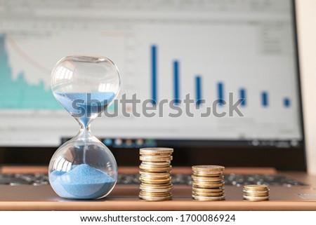 Flowing blue sand in hourglass symbolizing market resistance and financial crisis together with defocused financial graphs on laptop monitor on background. #1700086924