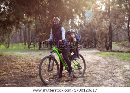 Mom and child in helmets ride a bike in the forest. Family bike ride in nature. The boy is sitting in a bicycle seat. #1700120617