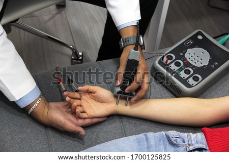 doctor's hands conducting electromyography study and nerve conduction in young woman Royalty-Free Stock Photo #1700125825