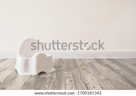 white baby potty on the floor. white pot on a white background. pot on the wooden floor. pot on a white wall background. children's pot in a bright interior. learn to go to the toilet. large space  #1700181343