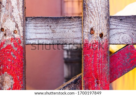 Old and grungy wooden fence with peeling red paint, close-up. Rough-hewn picket made of textured plank slats, background. Part of a painted wooden structure with an interesting texture and pattern  #1700197849