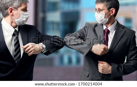 Two businessmen with a medical mask on their faces greet in a new way, striking with their elbows instead of a handshake. Social distance during the coronavirus epidemic #1700214004