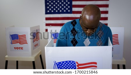 MS front view African American man in blue sweater and wearing a silver cross on a chain casting vote in booth at polling station. US flag on wall in background #1700215846