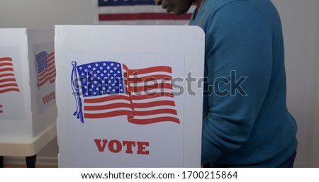 MS side view African American man in blue sweater and face hidden, casting vote in booth at polling station. US flag on wall in background #1700215864