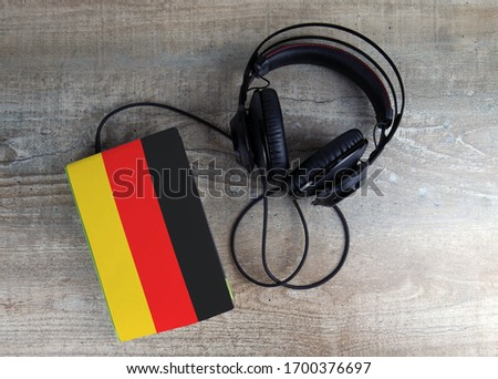 Headphones and book. The book has a cover in the form of Germany flag. Concept audiobooks. Learning languages. #1700376697
