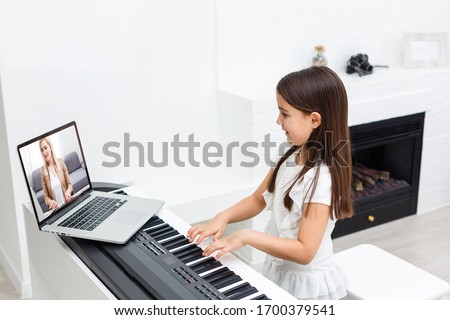 Scene of piano lessons online training or E-class learning while Coronavirus spread out or covid-19 crisis situation, vlog or teacher make online piano lesson to teach students pupils learn from home. #1700379541