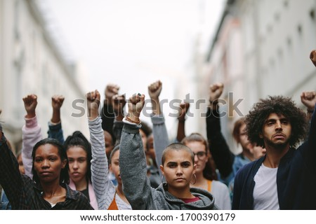 Group of protestors with their fists raised up in the air. Activists protesting on the street. #1700390179