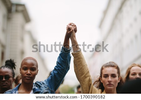 Group of activists with holding hands protesting in the city. Rebellions doing demonstration on the street holding hands. Royalty-Free Stock Photo #1700390182