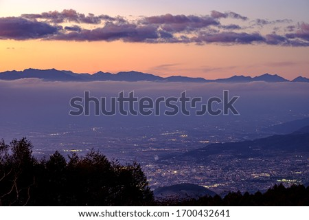 A Beautiful Aerial Photo of Shiojiri Town and North Alps under the Twilight Sunset Cloudy Sky Viewed from the Top of Takabotchi Plateau in Nagano, Japan.  #1700432641