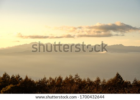 A Beautiful Aerial Photo of Shiojiri Town and North Alps under the Twilight Sunset Cloudy Sky Viewed from the Top of Takabotchi Plateau in Nagano, Japan.  #1700432644