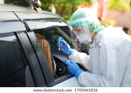 Doctor or nurse wearing PPE, N95 mask, face shield  and personal protective gown standing beside the car/road screening for Covid-19 virus, Nasal swab Test.