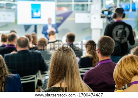 Audience listens lecturer at workshop in conference hall Royalty-Free Stock Photo #1700474467