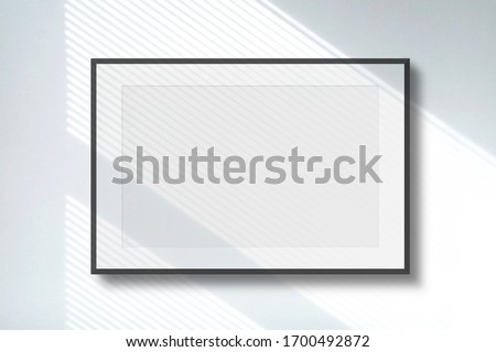 Blank picture frame on white wall with window shadow light as template for event promotion, design presentation, self portfolio etc.
