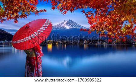 Asian woman wearing japanese traditional kimono at Fuji mountain. Autumn at Kawaguchiko lake in Japan. #1700505322