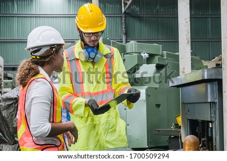 man and women Industrial engineers wearing safety uniform and hard hats with tablet working heavy industry in factory. #1700509294