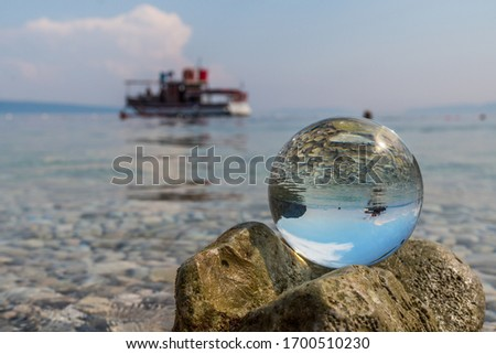 Crystal ball on stones near the sea. Original upside down view and rounded perspective of the sky, pebble seabed and boat. Original and engaging picture.