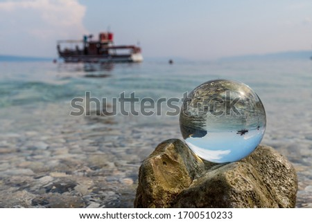 Crystal ball on stones near the sea. Original upside down view and rounded perspective of the sky, sea and boat. Original and engaging picture.